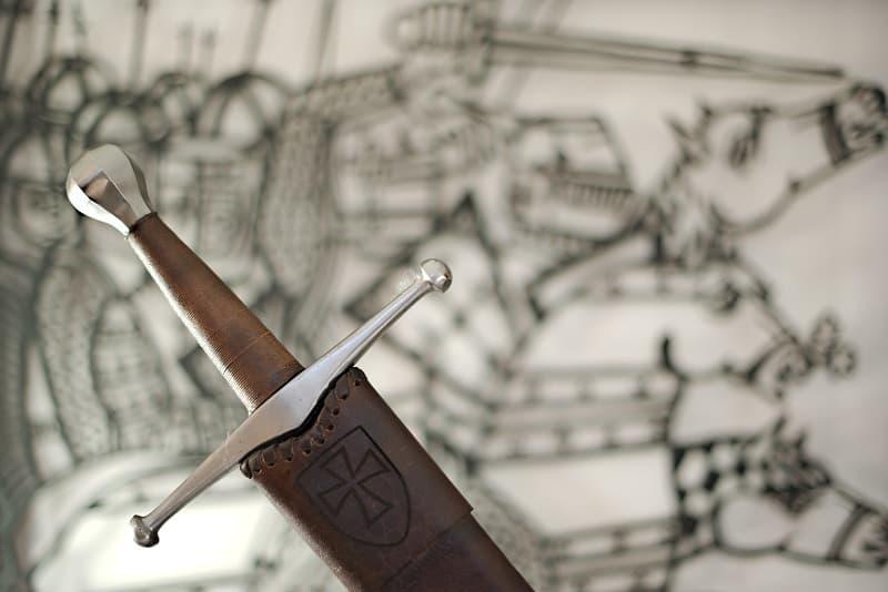 Épée médiévale de combat, pommeau en sphère facettée, fourreau en cuir brun avec blason et croix pattée