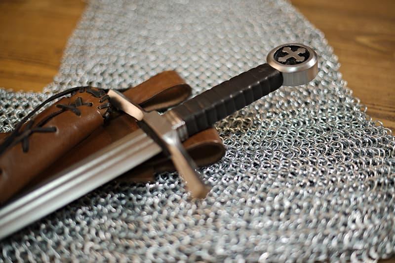 Épée de frappe, pommeau croix tréflée et fourreau cuir brun lacé, porté oblique