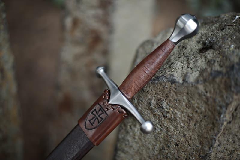 Dague de combat, pommeau croix tréflée et fourreau cuir brun lacé, porté oblique