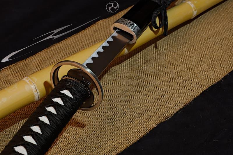 Katana de décoration, saya noire arborant un Mitsu Tomoe, kashira, tsuba et koiguchi Mitsu Tomoe | Signe distinctif depuis la nuit des temps, je continue à identifier les armoiries comme les logos. Les trois « gouttes » (magatama 曲玉) qui me composent donnent le mouvement, vers la droite ou la gauche.