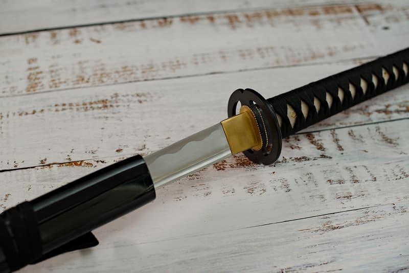 Katana tranchant avec monture noire, tsuba Miyamoto Musashi, livré avec une housse de protection en tissu (version luxe : dans un coffret en bois composite avec un support en bois verni avec protections et un kit d'entretien) | XVIIᵉ siècle, province de Musashi (région de Tōkyō). Forgée par Nagakuni, mon appartenance a été gravée sur ma soie (nakago 茎), discrètement, mais de manière indélébile.