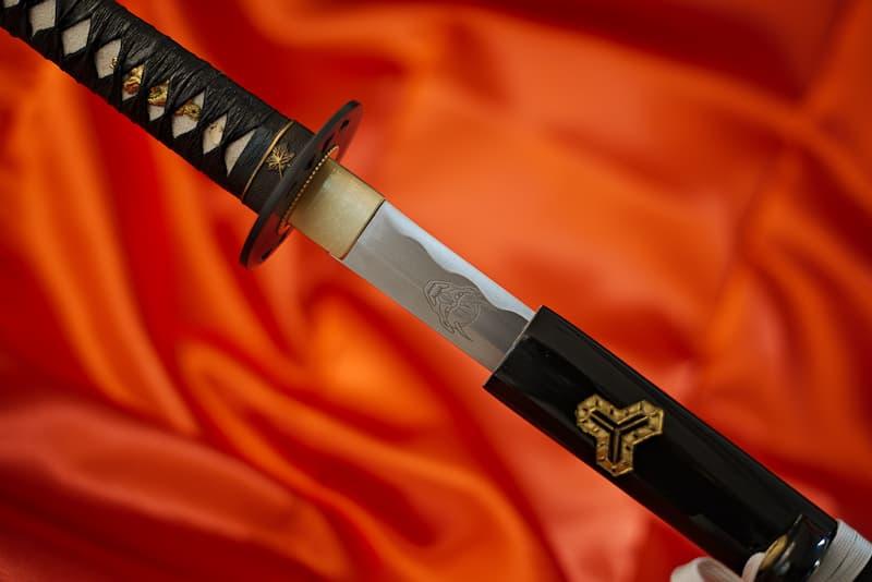 Katana affûté, lame gravée, fourreau (saya 鞘) en bois laqué noir décoré, ito en cuir noir, sageo argentée, livré avec une housse de protection en tissu | Je l'ai servi sans me soucier de la légitimité de ses actes. J'ai tranché des membres, ôté des vies à de multiples reprises. Forgée par Hattori Hanzō, je fus le prolongement de ses bras, la lame qui concrétisait son ambition sans limites.