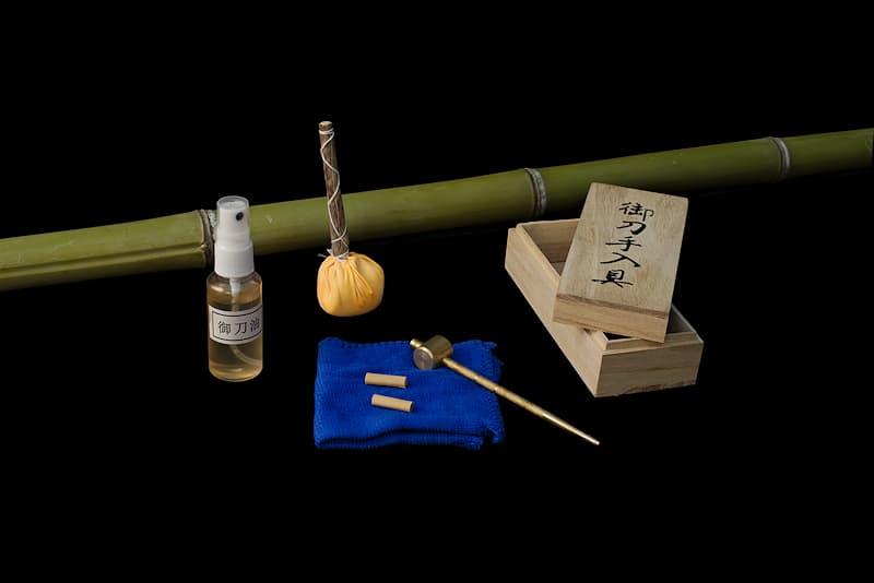 Huile de protection, micro-fibre, boule de craie (Uchiko), chasse goupilles (Mekugi Nuki) et goupilles (Mekugi), livrés dans une boîte en bois | J'ai le privilège d'entretenir les katanas des meilleurs samouraïs. J'en entretiens la lame pour la protéger des attaques de l'oxydation. En effet, les aciers non alliés (sans adjuvants comme le chrome et le molybdène) sont exposés à la rouille. Alliage de fer et de carbone, l'acier est fragilisé par la présence d'oxygène. L'air peut donc l'attaquer et c'est la raison pour laquelle mon huile permet de protéger la surface de ce noble métal.