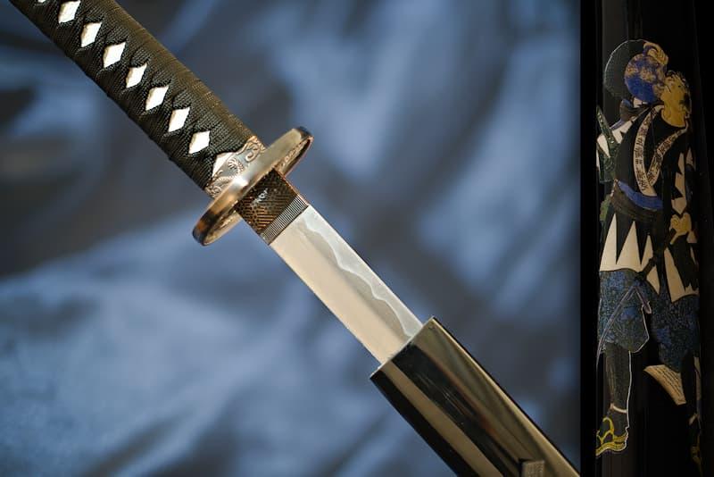 Katana de collection, saya noire avec samouraï armé d'une naginata sérigraphié, tsuba dragon | Je porte encore l'image de mon maître samouraï. Armé de ses deux sabres - katana et wakizashi - mais également d'une naginata (薙刀). Cette arme singulière permettait de combattre un guerrier à pied, mais elle était surtout utilisée pour briser l'élan des cavaliers en coupant les jarrets de leurs chevaux. En cette sombre période, il était nécessaire de ruser pour se défendre et survivre.