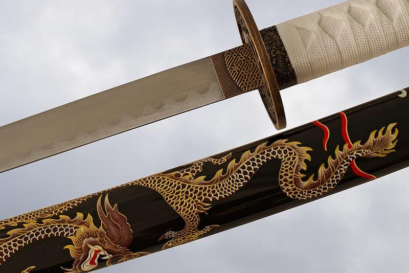 Katana de collection avec saya (鞘) noire décorée d'un dragon sérigraphié, tsuba (鍔) dragon, tsuka-ito (柄糸) et sageo (下緒) blanches | La légende raconte que j'ai été forgée dans le ventre du Dragon céleste. Le maître forgeron voulant sauver son fils dévoré vivant par l'animal, pris le même chemin. Après l'avoir retrouvé, il se mit à chercher des matériaux avalés par le monstre et permettant de forger une lame.
