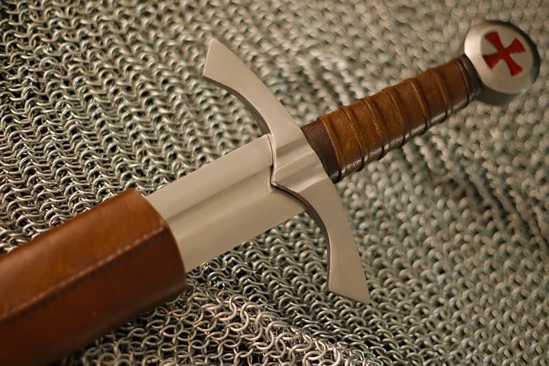 Épée médiévale forgée, pommeau circulaire avec croix pattée rouge, lame à gorge, fourreau en cuir brun et noir avec baudrier réglable