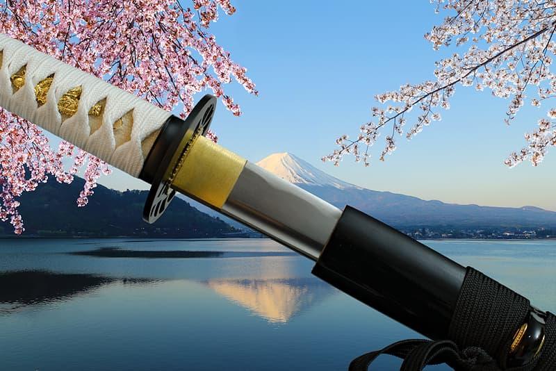 Katana tranchant avec fourreau (saya 鞘) en bois laqué noir, sageo (下緒) noire, tsuka-Ito (柄糸) blanche, livré avec une housse de protection en tissu | Je porte le nom de la force vitale liée à la floraison des arbres, symbole de la vie terrestre délicate et fragile, comme les fleurs de cerisiers. Connue également sous le nom de Sengen-sama, elle est le kami féminin (神, divinité ou un esprit shintoïste) du Mont Fuji (富士山 Fujisan), la plus haute montagne du Japon.