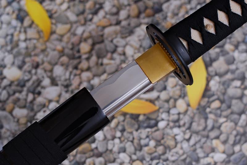 Sabre japonais d'entraînement non affûté pour la pratique du iaïdō (居合道 l'art de dégainer le sabre), lame en aluminium, livré avec une housse de protection en tissu noir | Je n'ai pas été forgée. La matière dont je suis fabriquée, l'aluminium, est le deuxième métal le plus utilisé par l'industrie actuelle. Très léger, avec une excellente résistance à la corrosion ce métal permet aux pratiquant.e.s de s'entraîner sans risque de fatigue ou de tendinite.