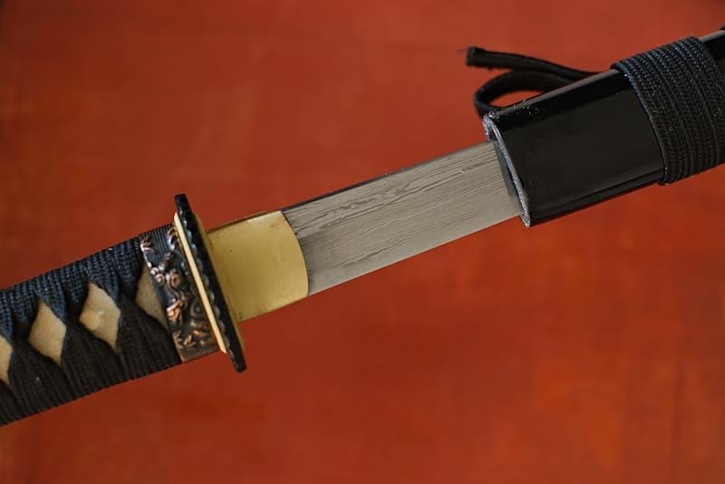 Tantō (短刀) lame forge Damas tranchante avec fourreau (saya 鞘) en bois, livré une housse de protection en tissu, dans un coffret en bois | Les vagues caractéristiques de ma fabrication feuilletée décorent mes flancs. Plié et replié sur lui-même, l'acier avec lequel j'ai été forgée revêt cette signature que j'honore.