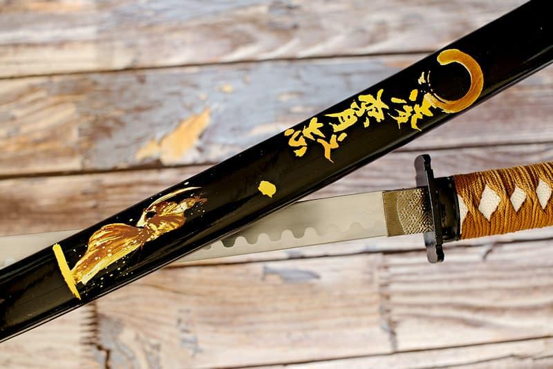 Katana de collection avec saya (鞘) noire sérigraphiée (samouraï et kanjis calligraphiés), tressages bruns | Mon maître fut surnommé le « Samouraï d'or », en référence à sa résilience et à sa capacité à transformer ses blessures en nouvelles passes d'armes. Il vécut entre les XIVᵉ et XVᵉ siècles, à la période durant laquelle le Japon donna naissance à cet art de réparer les objets cassés en soulignant ses cicatrices avec de la poudre d'or.