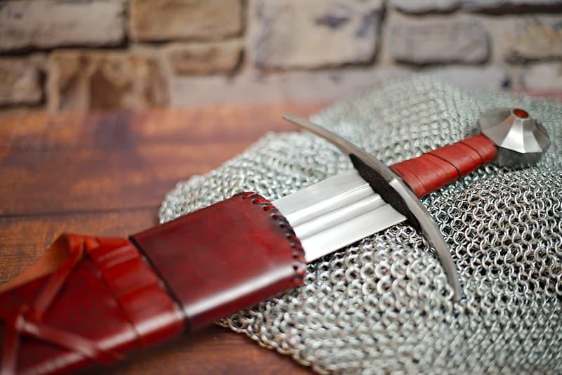 Épée médiévale forgée XIIᵉ / XIIIᵉ siècle, lame à effet ressort à double gorge, fourreau en bois et cuir rouge sombre avec ceinture en cuir