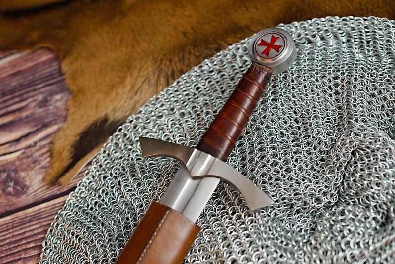 Épée médiévale forgée, pommeau circulaire avec croix pattée rouge des chevaliers templiers, lame à gorge, fourreau en cuir brun et noir avec baudrier réglable