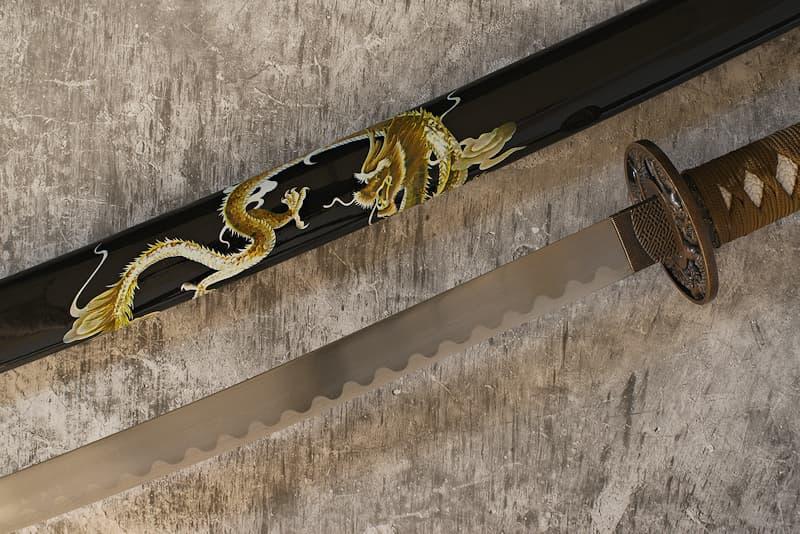 Katana de collection avec saya (鞘) noir décoré d'un dragon sérigraphié, tsuba (鍔) dragon, tsuka-ito (柄糸) et sageo (下緒) marron   Mon saya est décoré d'un dragon. Ce n'est pas n'importe lequel. Il s'agit du dragon « joueur ». Il a été ainsi surnommé, car il apparaît et disparaît comme bon lui semble, faisant basculer ses victimes dans la folie.